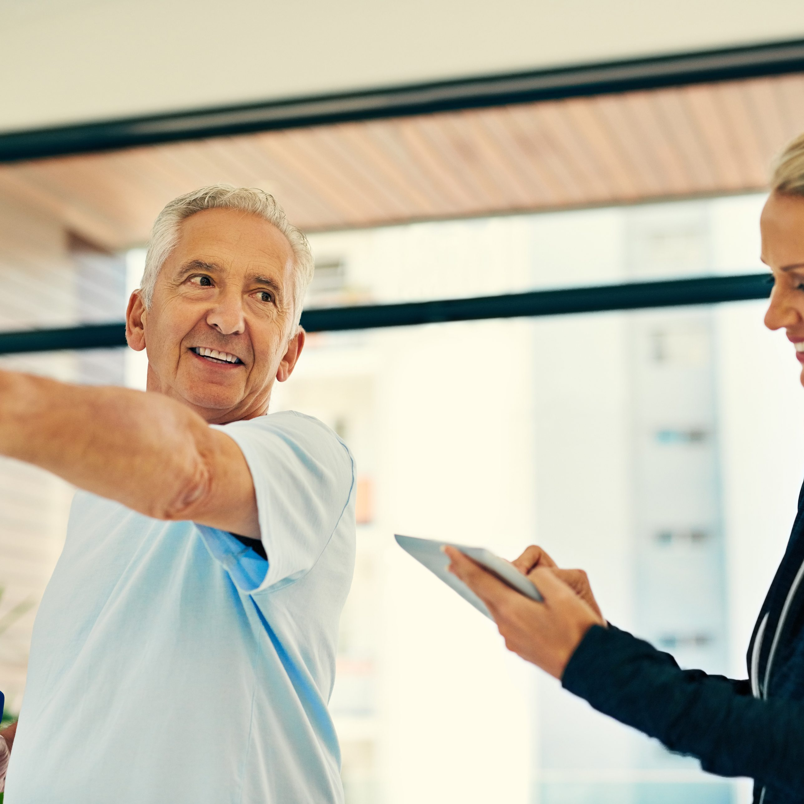 Shot of a happy physiotherapist tracking her senior patient's progress on a tablet while he lifts weights