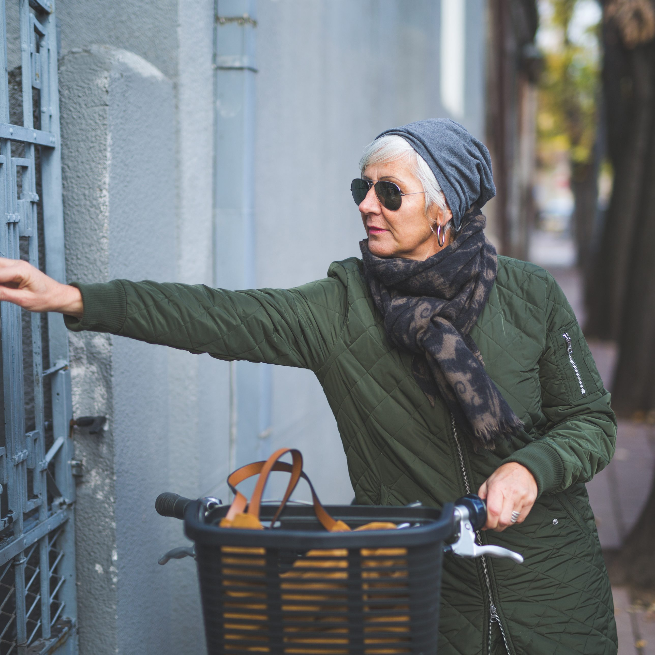 Senior woman arriving home with bicycle and taking mail out of mailbox